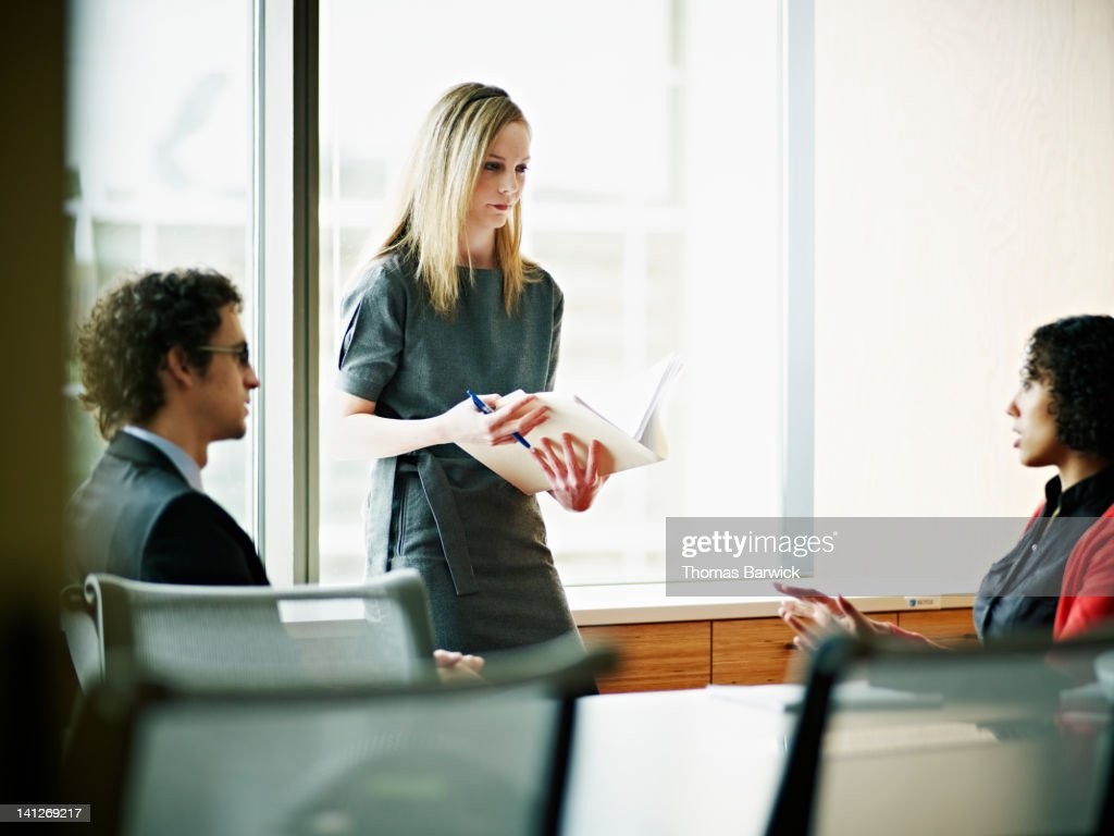 Three coworkers in discussion in conference room : Stock Photo