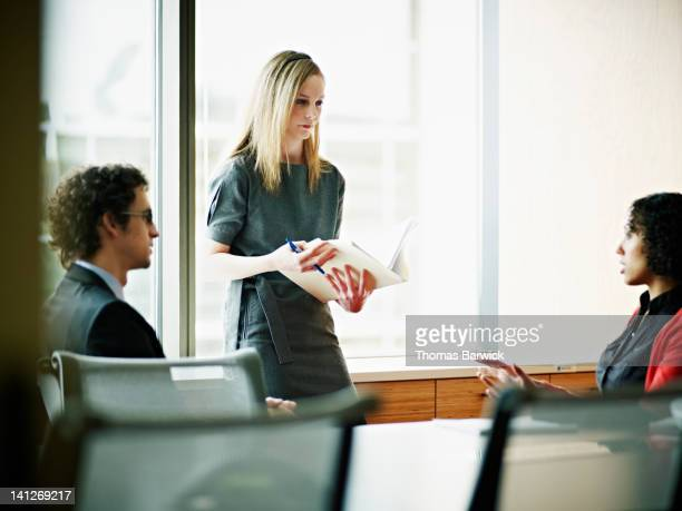 Three coworkers in discussion in conference room