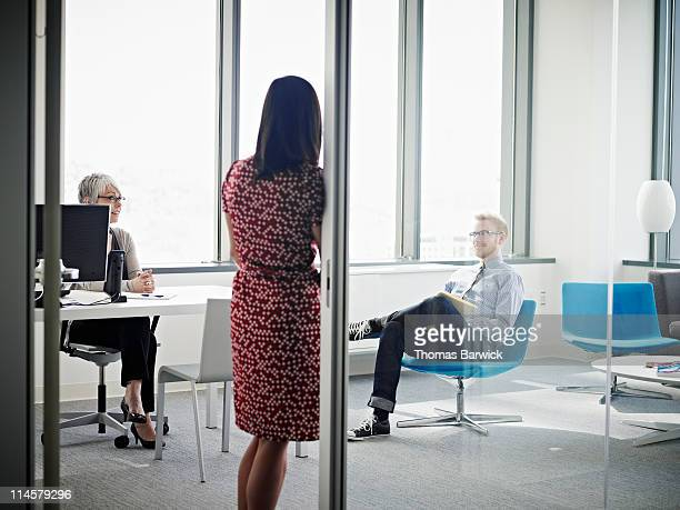 three coworkers in discussion in corner office - leanintogether stock pictures, royalty-free photos & images