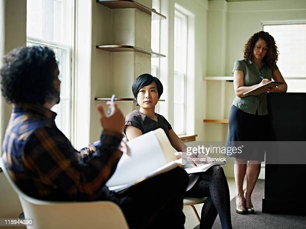 Three coworkers in discussion in office