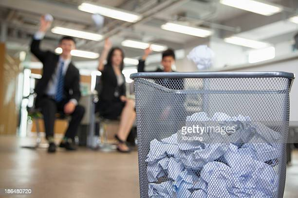Three coworkers preparing to throw paper into waste basket