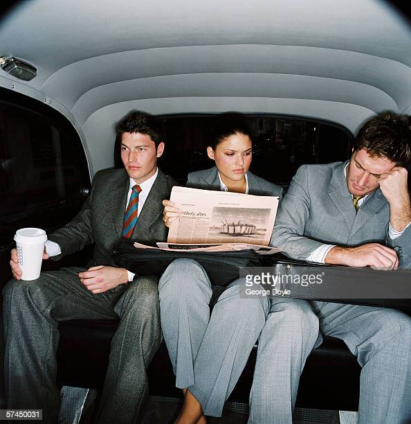 three co-workers sitting in the backseat of a car; tired