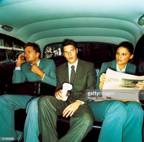 three co-workers sitting in the backseat of a car; waiting