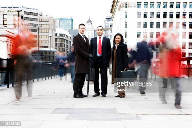 Three coworkers stand on bridge surrounded by moving figures