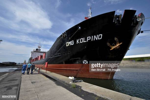 Three crew members walk around the OMG Kolpino Russian cargo ship pictured at Avonmouth docks Bristol where its crew of 12 sailors have been marooned...