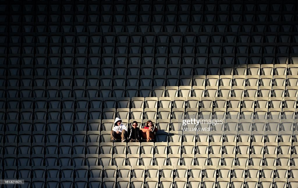 Three cricket fans watch Australia play the West Indies in their one-day cricket international played at the Melbourne Cricket Ground (MCG), on February 10, 2013. AFP PHOTO/William WEST IMAGE