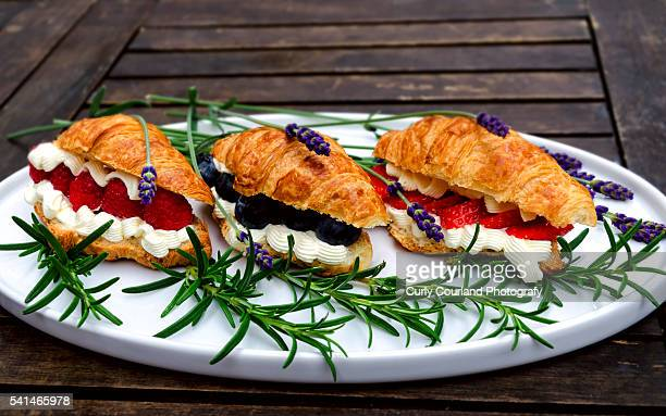 Three croissant stuffed with creme fraiche, blueberries, raspberrries and sliced strawberries, surrounded by rosemary and lavender on the white oval dish on the vintage wooden table