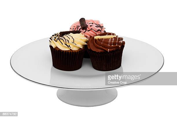 Three cupcakes on white cake stand