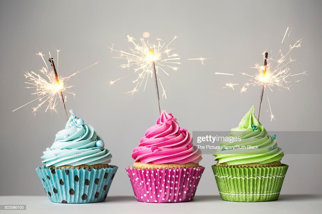Three cupcakes with sparklers : Stock Photo