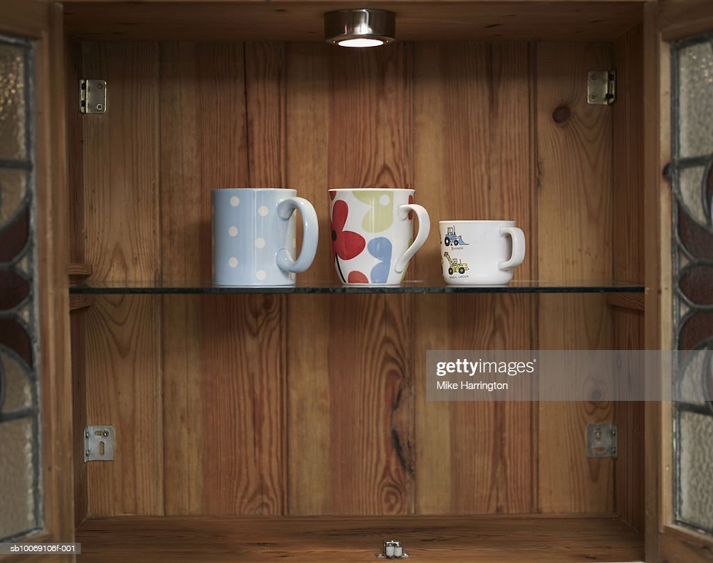 Three cups in cabinet : Stockfoto
