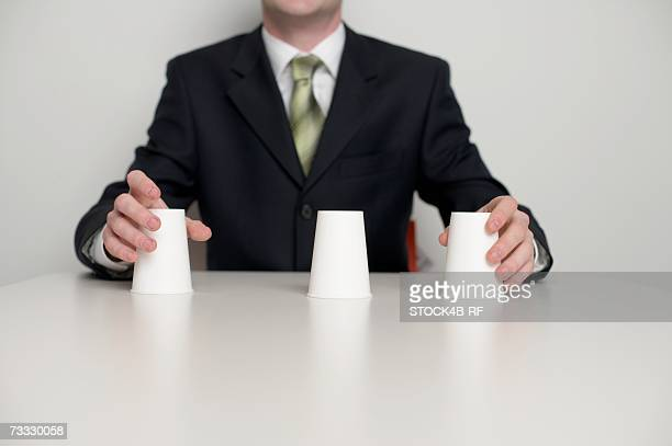 Three cups in front of a businessman, shell game