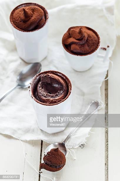 Three cups of vegan mousse au chocolat, tea spoons, cloth on white wood