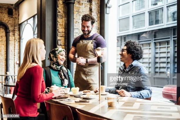 Three customers sitting at table talking and smiling with waiter