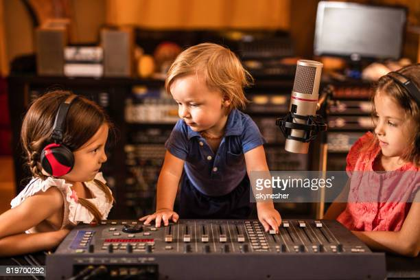 Three cute kids having a radio broadcast in a station.