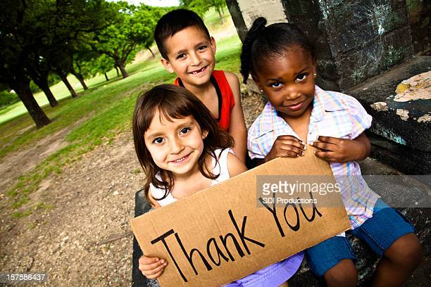 three cute kids smiling and holding a thank you sign - thank you phrase stock pictures, royalty-free photos & images
