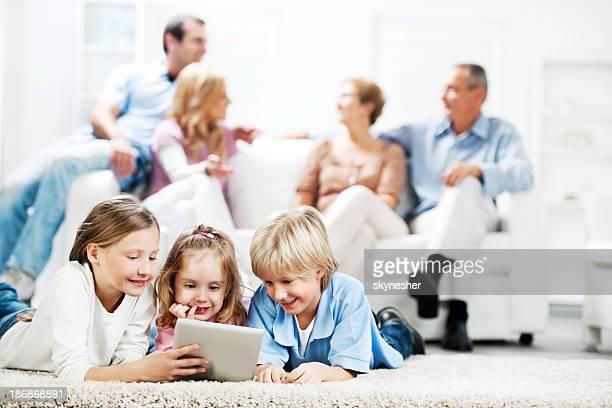 Three cute kids using a digital tablet.