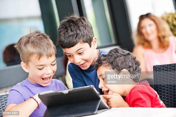 Three cute kids using a digital tablet