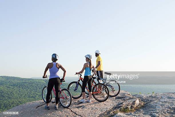 Three cyclists looking at view