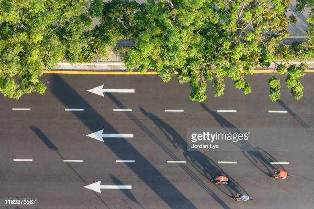 three cyclists riding on tar road, aerial view - tar stock pictures, royalty-free photos & images
