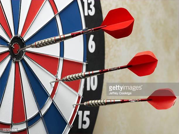 Three darts in a row, one in bullseye, on dart board, close-up