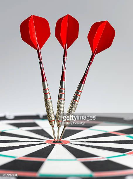 three darts in bulls eye of dart board, side view, close-up - sports target stock pictures, royalty-free photos & images