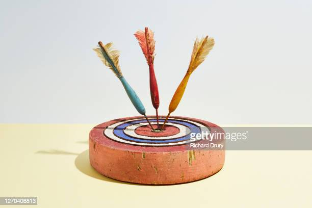 three darts in the bull's-eye of a dartboard - richard drury stock pictures, royalty-free photos & images