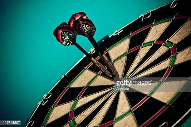 tres de dardos en bullseye, primer plano - penetrar fotografías e imágenes de stock
