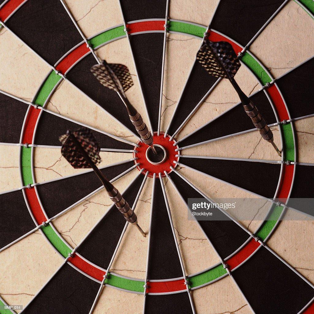 Three Darts On Dartboard One In Bullseye ストックフォト - Getty Images