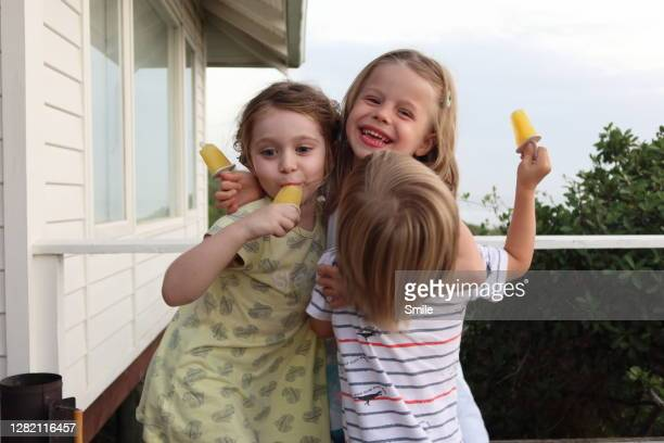 three delighted young children embracing with ice lollies - first occurrence stock-fotos und bilder