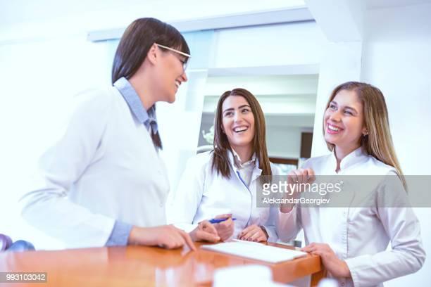 führt zu drei zahnarzt techniker diskutieren die tage - arzthelferin stock-fotos und bilder