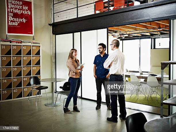 Three designers in discussion near conference room