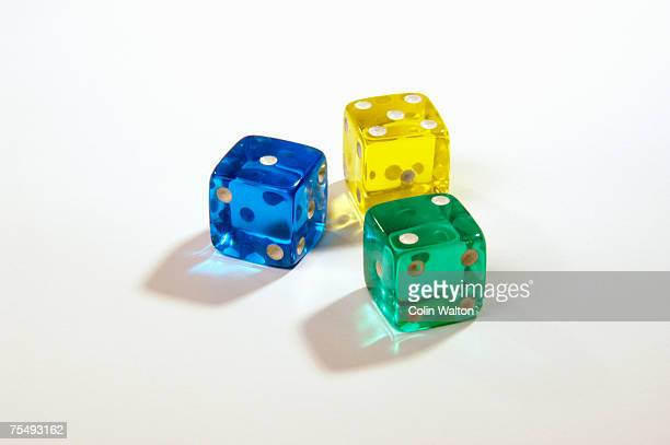 Three dice, made from blue, green and yellow transparent glass