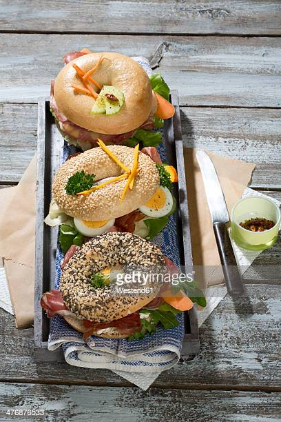Three different bagels garnished with salami, sausage, slices of bacon, rocket salad, lettuce, cucumber carrot, egg, cream cheese and cress and parsley