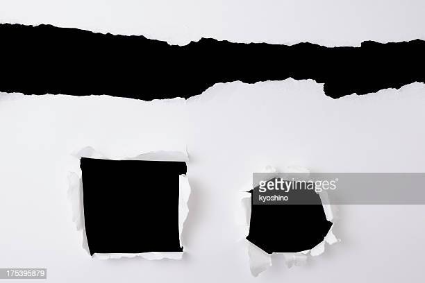 Three different holes in the white paper on black background