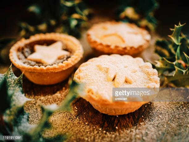three different mince pies against a dark wood board arranged holly and dusted with icing sugar for snow effect. - wood effect stock photos and pictures