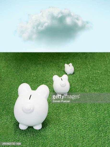 three different sized piggy banks on artificial green grass, rear view - turf stock pictures, royalty-free photos & images