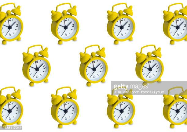 three dimensional yellow alarm clocks against white background - westeuropa stock-fotos und bilder