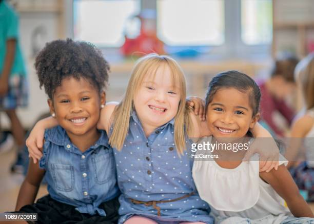 three diverse friends at kindergarten - down syndrome stock pictures, royalty-free photos & images