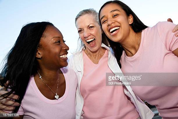 Three Diverse Friends in Pink Laughing Together
