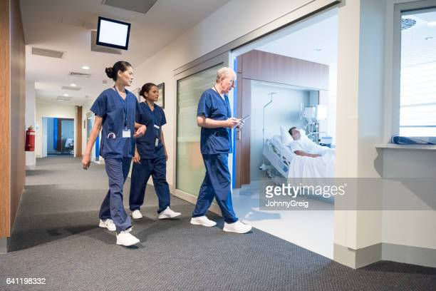 Three doctors and nurses walking down hospital corridor and entering ward
