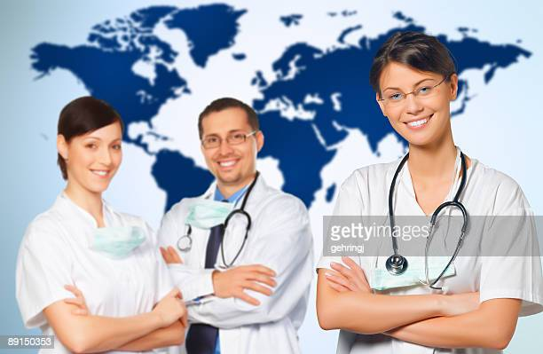 Three doctors in front of a world map