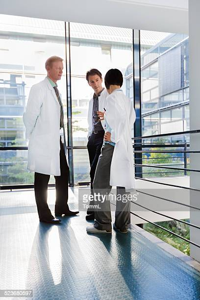 Three Doctors Standing In Bright Hospital Corridor And Discussing