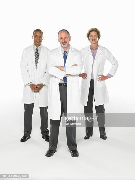 Three doctors standing on white background, portrait