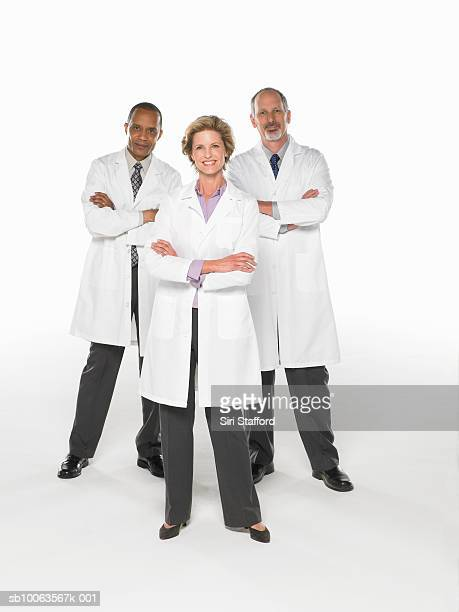 Three doctors standing on white background with arms crossed, portrait