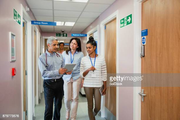 three doctors walking down the corridor - doctor's surgery stock pictures, royalty-free photos & images