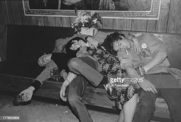 Three drinkers at an Irish bar one wearing a 'Victory To The IRA' badge sleep on top of each other at closing time New York City circa 1978