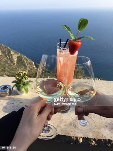 Three drinks cheersing overlooking the Mediterranean Sea