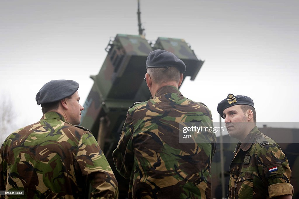 Three Dutch soldiers stand in front of a Dutch Patriot defence missile prior to the transportation of the missiles from their base in Vredepeel, The Netherlands, on January 7, 2013, to the Eems harbor in Groningen. The missiles will be shipped to Turkey where they are to be used to protect the country from possible attacks from neighbouring Syria. AFP PHOTO/ EVERT-JAN DANIELS = netherlands out