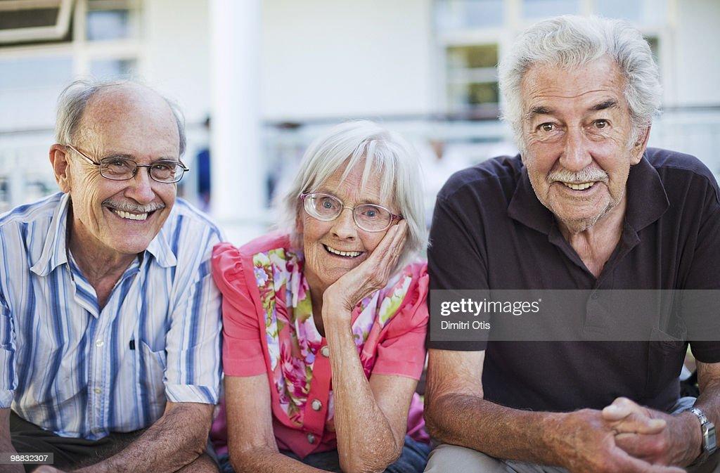 Three elder people on bench laughing : Stock Photo
