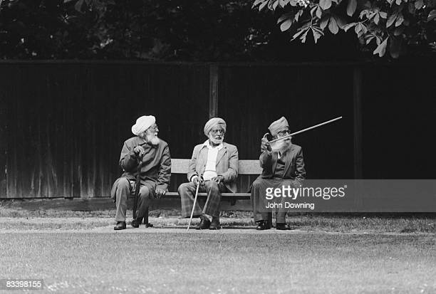 Three elderly Asian men on a bench in London's Southall circa 1980